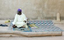 A marabout from a village in the Kolda region holding a rosary. The telephone connects him with migrants or their families. Next to it is a book and against the wall a tablet called a 'Halwaa', on which are written holy verses