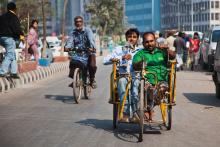 Two men in Dhaka drive a wheelchair